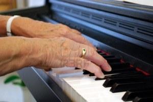 due-mani-di-una-donna-anziana-a-suonare-il-pianoforte