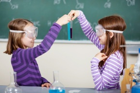Two little students doing biochemistry research at the classroom